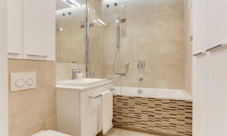 Aranżacja łazienki w beżach z mozaiką. W łazience znajduje się wanna z parawanem nawannowym składanym, duża umywalka oraz miska wc.