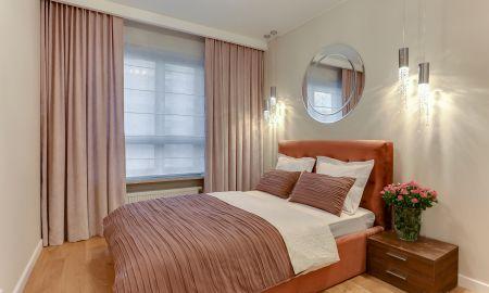 Aranżacja przytulnej sypialni, łóżko z tapicerowanym zagłówkiem, lampy z kryształkami, lustro w sypialni.