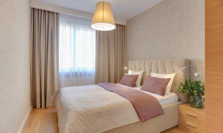 Łóżko tapicerowane w sypialni z pojemnikiem w beżach, ściany pokryte tapetą.