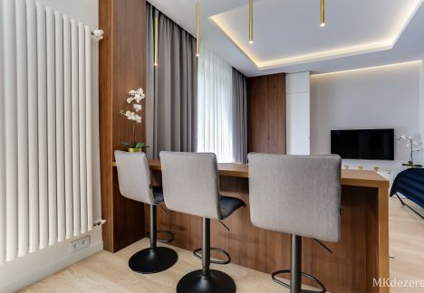 Barek oddzielający kuchnię od salonu ze stołkami barowymi. Na ścianie, grzejnik dekoracyjny.