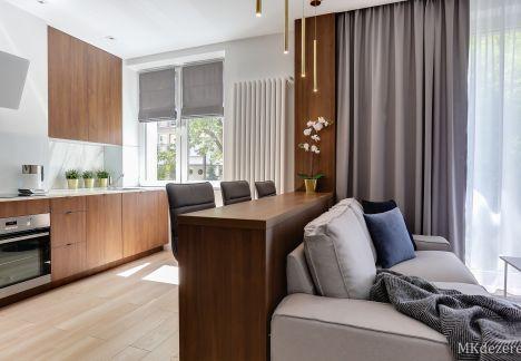 Kuchnia połączona z salonem. Ciemne meble, połączone są z jasnym drewnem i meblami w białym kolorze.