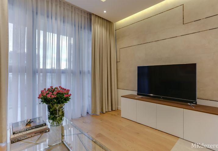 Elegancka zabudowa ściany telewizyjnej oświetlona dekoracyjnym światłem ukrytym w suficie podwieszanym.