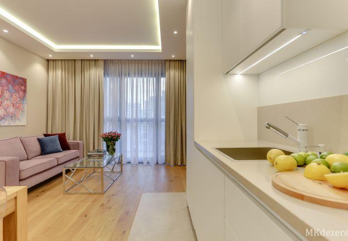 Aranżacja białej kuchni połączonej z salonem. Całe mieszkanie utrzymane w kolorach beżu i bieli z kroplą koloru.