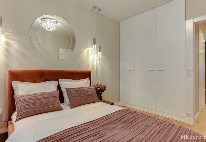 W sypialni oprócz łóżka z tapicerowanym zagłówkiem, znalazła się duża biała szafa.