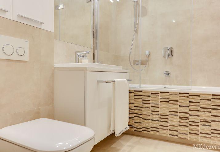 Nowoczesna, jasna łazienka z mozaiką na wannie.