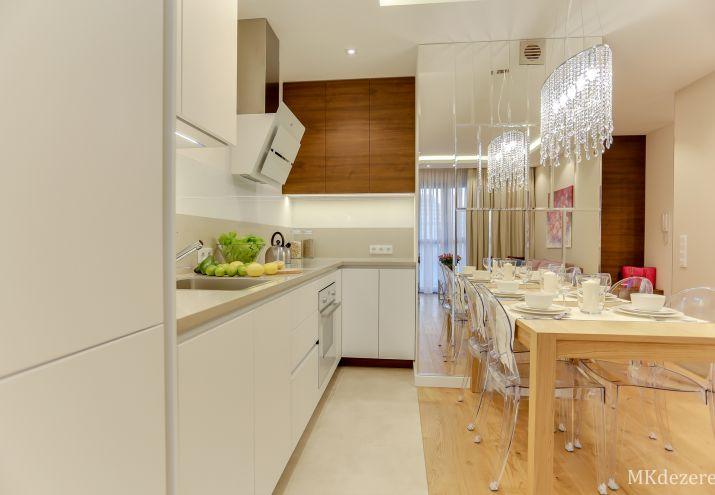 Aranżacja małego salonu z drewnianym stołem, duże lustro, blat w kuchni z kamienia, białe meble, lampa z kryształkami nad stołem.