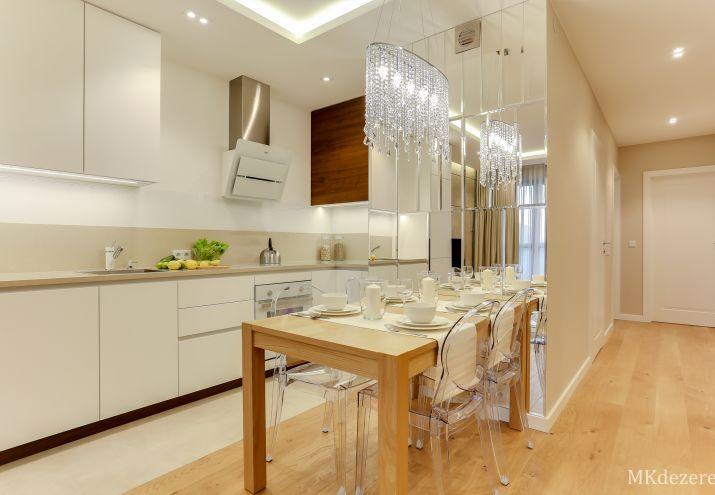 Stół w kuchni przy ścianie z przezroczystymi krzesłami. Na ścianie umieszczone dekoracyjne lustra w których odbija się żyrandol z kryształkami.