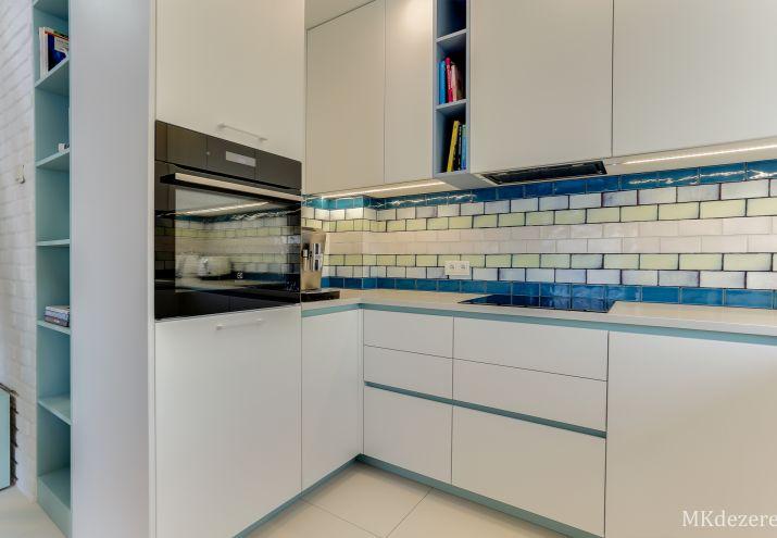 Białe płytki w kuchni na podłodze i na ścianie w połączeniu z niebieskimi i zielonymi płytkami.