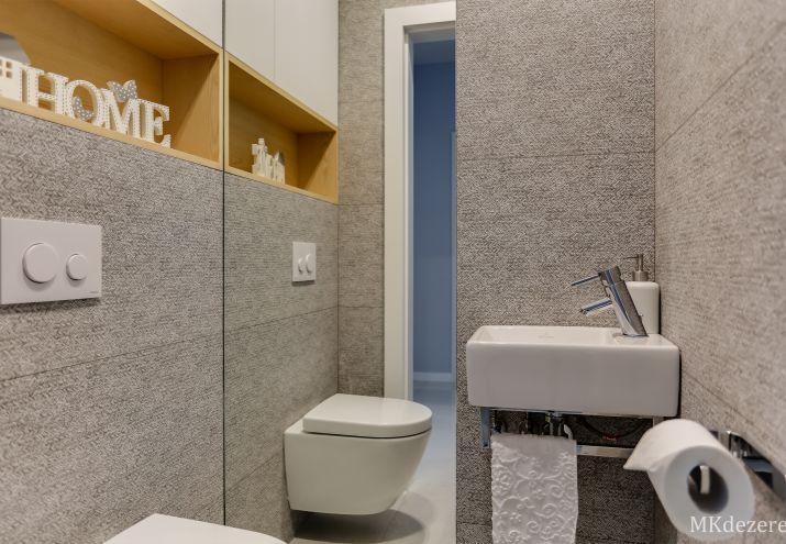 Aranżacja małej łazienki z wc w szarościach.