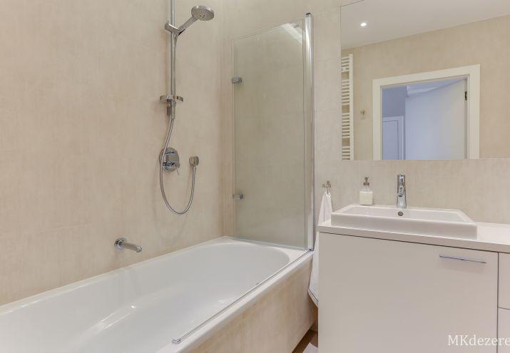 Łazienka z wanną i prysznicem. Na wannie znajduje się duży parawan na-wannowy.
