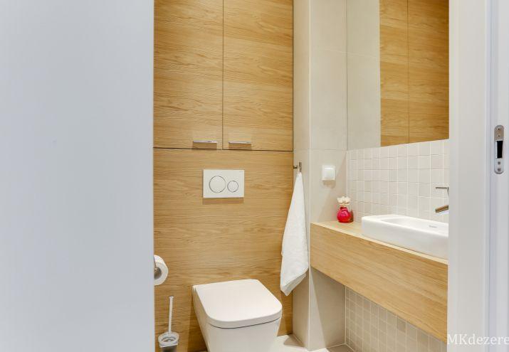 Łazienka z wc, mała umywalka stojąca na drewnianym blacie.
