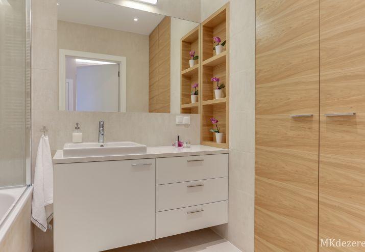 Aranżacja łazienki z dużą szafką oraz wbudowaną umywalką. Pralka zabudowana w szafie.