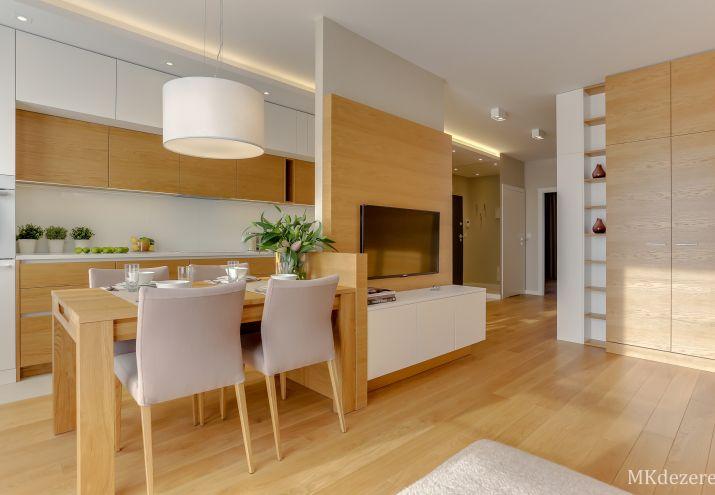 Stół oddzielający kuchnię od salonu. Na ścianie wiszący telewizor.
