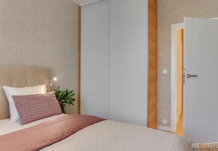 W sypialni znajduje się duża szafa z drzwiami przesuwnymi.