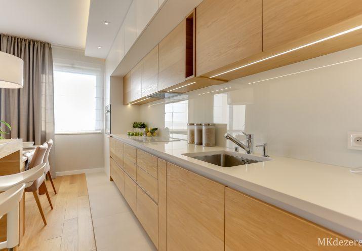 Biała lakierowana kuchnia połączona z ciepłym drewnem.